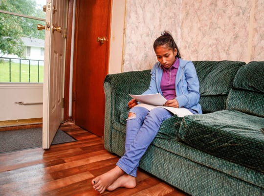 Des Moines Hoover graduate Khein Thein spends time reading from a college prep textbook at her home in Des Moines on Tuesday, May 28, 2019.