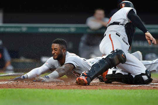 Detroit Tigers' Niko Goodrum, left, is safe at home, as Baltimore Orioles catcher Austin Wynns tries to make the tag, after a double by Nicholas Castellanos during the fourth inning of a baseball game Wednesday, May 29, 2019, in Baltimore.