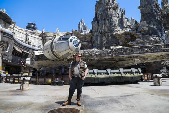 "A Disney cast member stands in front of The Millennium Falcon: Smugglers Run ride, inside the new ""Star Wars: Galaxy's Edge,"" at Disneyland Resort, in Anaheim, Calif., May 29, 2019. (Jay L. Clendenin/Los Angeles Times/TNS)"