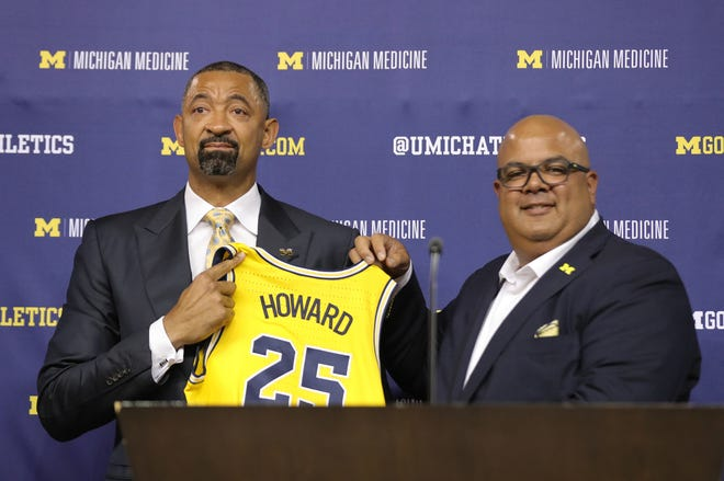 Juwan Howard becomes emotional as poses for a photo with University of Michigan athletic director Warde Manuel as the new head basketball coach during a press conference on Thursday, May 30, 2019 at Crisler Center in Ann Arbor, Mich.