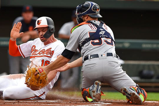 Baltimore Orioles' Trey Mancini, left, is safe at the plate, as Detroit Tigers catcher John Hicks tries to make the tag, on a double by Renato Nunez during the first inning of a baseball game Wednesday, May 29, 2019, in Baltimore.