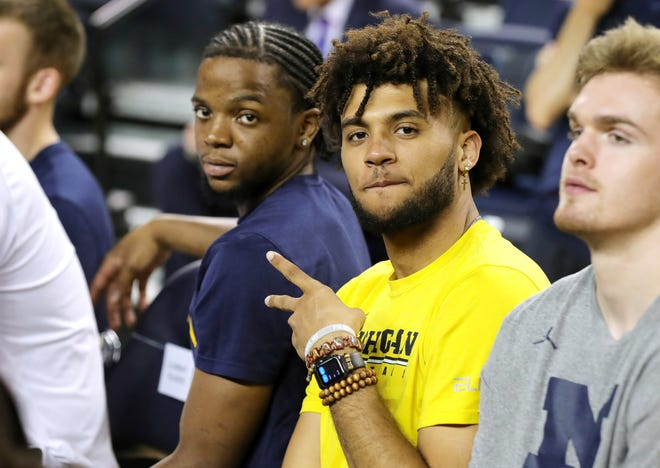 Michigan basketball players Zavier Simpson, left, and Isaiah Livers in the audience as new head coach Juwan Howard takes questions on Thursday, May 30, 2019 at the Crisler Center in Ann Arbor, Mich.
