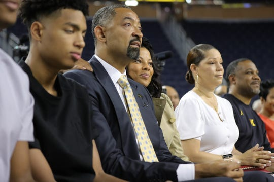 Juwan Howard sits with his wife Jenine,  as he waits to be introduced as the new Michigan basketball coach.