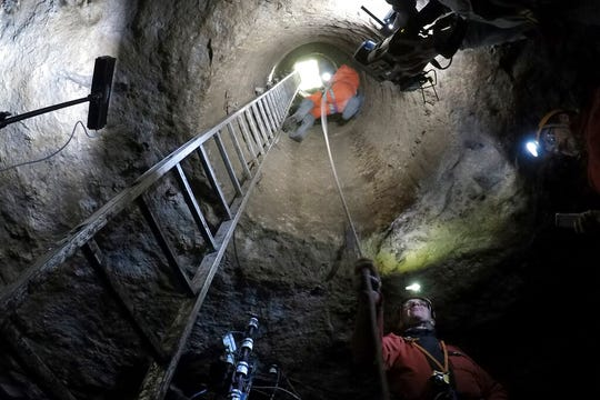In this photo taken on Friday May 17, 2019, spelunkers rappel down a well shaft into a quarry in Fleury-sur-Orne, near Caen, Normandy.