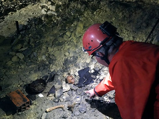 In this photo taken on Friday May 17, 2019 spelunker Laurent Dujardin points to artifacts left by WWII refugees in a quarry in Fleury-sur-Orne, near Caen, Normandy.