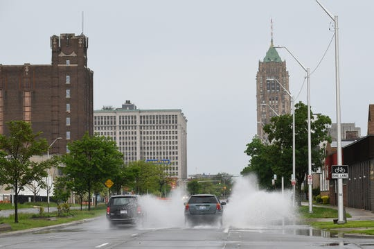 Vehicles drive on East Grand Boulevard through standing rain water on a rainy afternoon in Detroit on May 19.