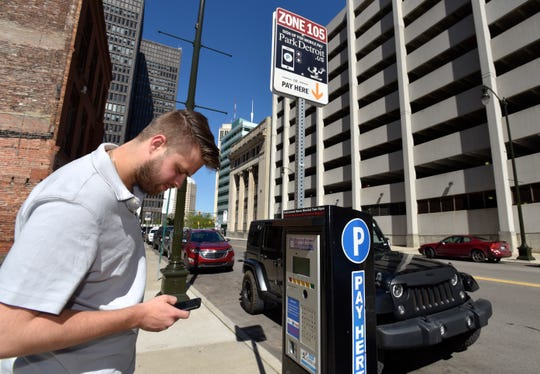Gjon July, 25, pays for parking on his Park Detroit cellphone app on Lafayette near Shelby. He works in downtown Detroit but lives in Macomb, so he would not be eligible for a discount on parking meter violations for Detroit residents.