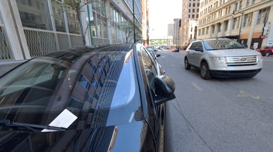 A parking ticket is tucked under the windshield wiper of a vehicle parked on Griswold near Fort in Detroit on May 23.