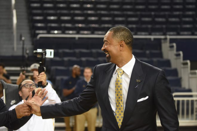 Juwan Howard shakes hands as he enters the Crisler Center in Ann Arbor for his first news conference.