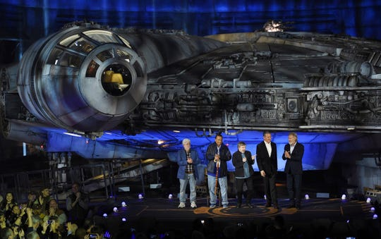From left, George Lucas, Billy Dee Williams, Mark Hamill, Bob Iger and Harrison Ford stand in front of the Millennium Falcon starship during a dedication ceremony for the new Star Wars: Galaxy's Edge attraction at Disneyland.