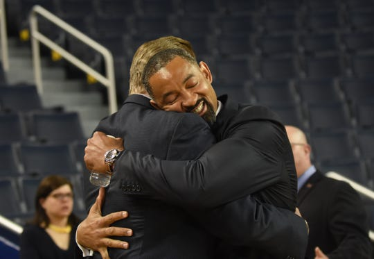 Juwan Howard embraces former Michigan basketball player Tim McCormick during the event.