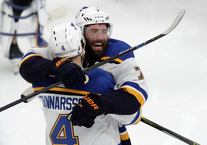 St. Louis Blues' Carl Gunnarsson (4) is congratulated by Pat Maroon, rear, after he scored the winning goal against the Boston Bruins during the overtime period.