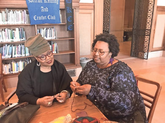 Jocelynn Brown watches as Gregg Burrell knits with wooden needles at a Detroit Knitting and Crochet Club meeting.