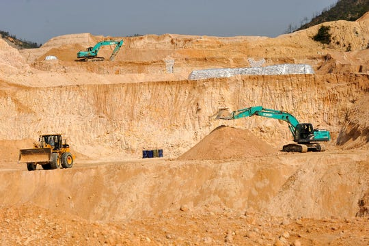 In this Dec. 30, 2010, photo, workers use machinery to dig at a rare earth mine in Ganxian county in central China's Jiangxi province. Facing new trade sanctions and a U.S. clampdown on its top telecommunications company, China issued a pointed reminder on Wednesday, May 30, 2019 that it has yet to unleash all its weapons in its trade war with the Trump administration. Chinese state media warned that Beijing could cut America off from exotic minerals that are widely used in electric cars and mobile phones.