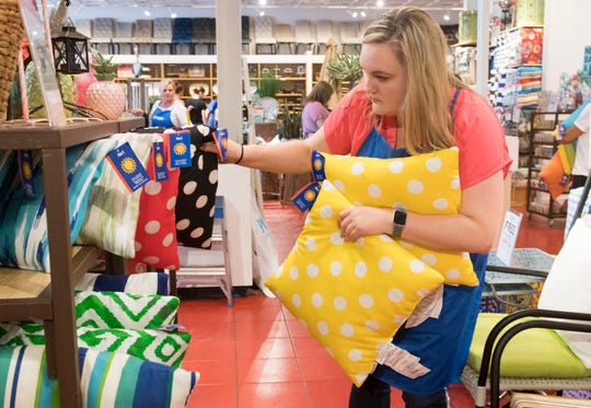 Amanda McMillian pulls pillows for a customer at Pier 1 Imports Saturday, May 25, 2019. McMillian works 15-18 hours per week at Pier 1 Imports in addition to  teaching Family and Consumer Sciences at North High School.