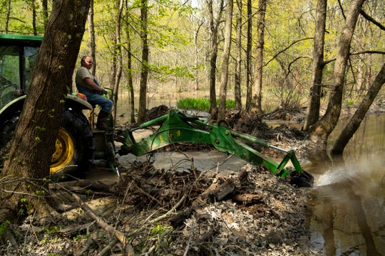 Andrew Mann uses an excavator attached to his tractor to tear out a section of beaver dam in the Twin Swamps Nature Preserve near Hovey Lake Fish & Wildlife Area Wednesday, April 17, 2019.