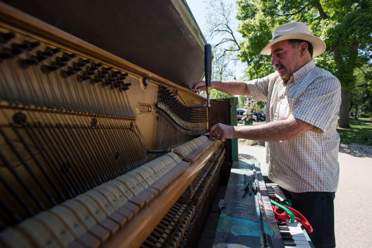 "Piano tuner Bob Otterman tunes up the ""Pianos About Town"" piano painted by local artist Terry McNerney in front of the Old Town Library on Thursday, May 30, 2019, in Fort Collins, Colo."