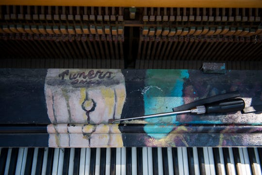 "Local artist Terry McNerney left left a message reading ""tuners only"" behind the front access panel of the ""Pianos About Town"" piano that tuner Bob Otterman tunes up in front of the Old Town Library on Thursday, May 30, 2019, in Fort Collins, Colo."