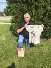 Peter Williams shows the Mickey Mouse T-shirt he wore while winning the WIAA state long jump title with Oakfield High School in 1972