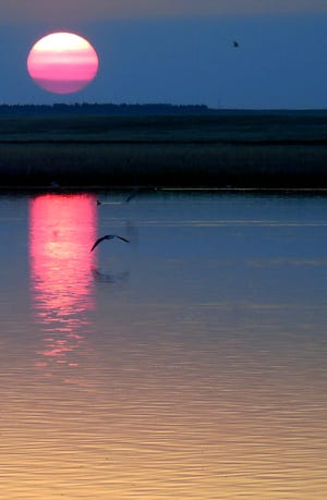 The sun sets at Benton Lake NWR through smoke from Alberta forest fires in late May. Sunrise and sunset are prime birdwatching times.
