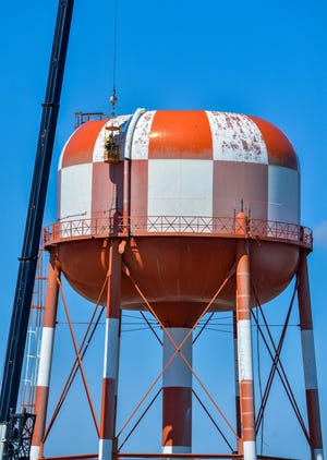Crews work on dismantling the red and white water tank on Gore Hill in late May. A new water tank was constructed last year across Interstate 15, next to the Crystal Inn Hotel & Suites.