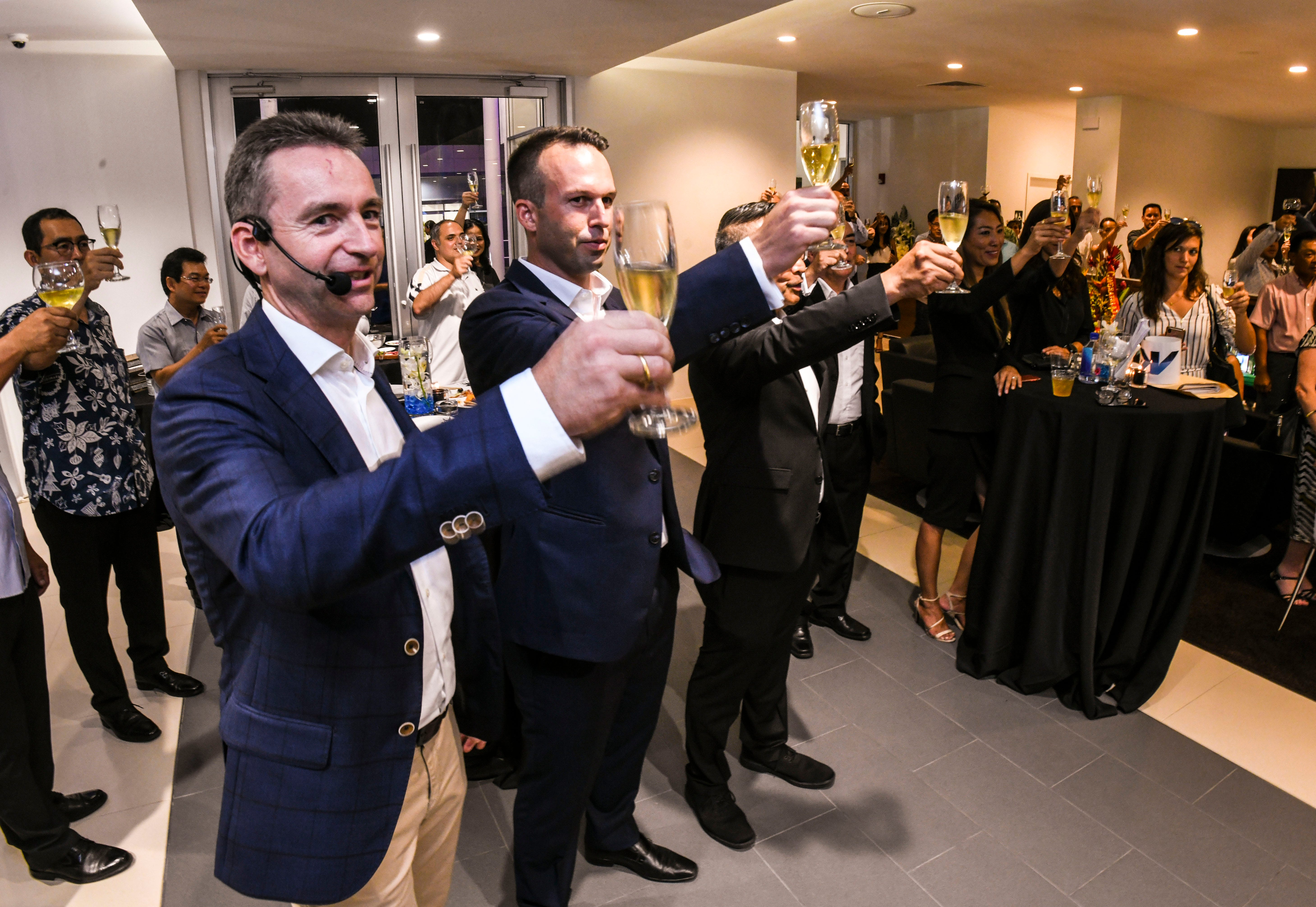 Christopher Wehner, front, BMW Group Asia managing director and Alex Hammett, Atkins Kroll, Inc. president, lead guests and employees in a champagne toast to celebrate the opening of the dealership's new BMW showroom in Tamuning on Wednesday, May 29, 2019.