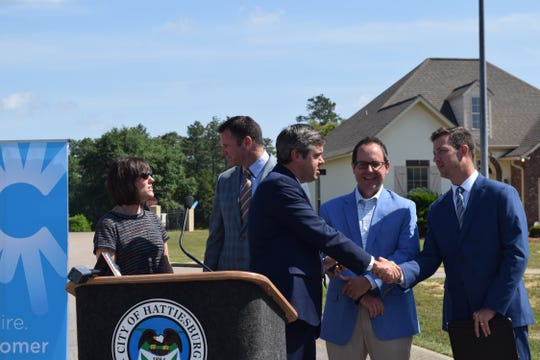 Hattiesburg Mayor Toby Barker shakes hands with C Spire Market Development Manager Chase Bryan during a news conference Thursday, May 30, 2019, at Shadow Ridge subdivision announcing fiber optic technology installation in the city.