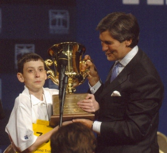 David Tidmarsh (left) still has tears in his eyes as he accepts the national spelling bee trophy in June of 2004.