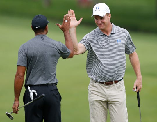 Former NFL player Peyton Manning, right, high fives with Tiger Woods after making a birdie putt during the pro-am round of the Memorial golf tournament Wednesday, May 29, 2019, in Dublin, Ohio.