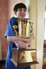 David Tidmarsh, 2004 winner of the National Spelling Bee, cradles the trophy he won in 2005.