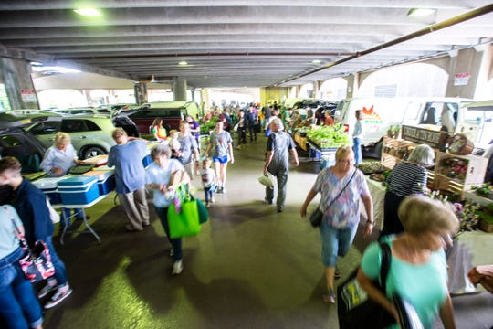 People stroll between booths during the Farmers Market, Wednesday, May 29, 2019, below the Chauncey Swan Parking Ramp, between Burlington and Washington Streets in Iowa City, Iowa.