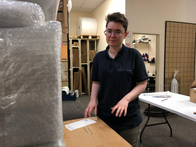 Recent University of Iowa English graduate Leah Parker, 23,  works at The UPS Store, while finishing writing her third book, on Thursday, May 30, 2019.