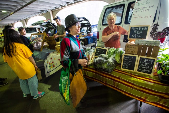 Nancy Olthoff, right, of Iowa City, helps out a friend at their Morning Glory booth during the Farmers Market, Wednesday, May 29, 2019, below the Chauncey Swan Parking Ramp, between Burlington and Washington Streets in Iowa City, Iowa. Morning Glory plans on opening a food truck later this summer.