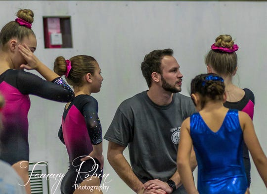 Alex Courville, center, the owner of Alex's Tumbling, talks with gymnastics students.