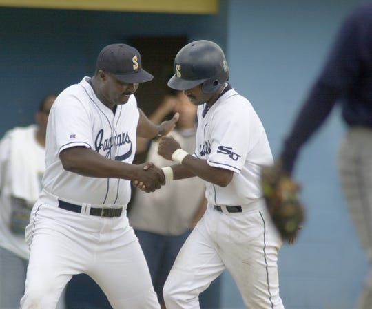 Southern head baseball coach Roger Cador (left) greets Chris Atwell with a handshake during a game with Jackson State on April 2, 2000.