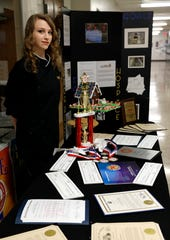 Bailee McCall stands next to many of the Lancaster High School culinary arts program's awards from the 2018-2019 school year. McCall won a number of awards this year including $20,000 in scholarship money through competitions this year. The program's graduating class was awarded more than$70,000 in scholarship money.