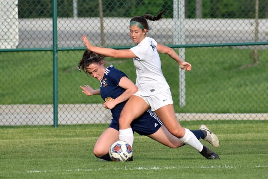 Novi's Jenna Daschke (right) and Hartland's Lauren Smith battle for the soccer ball in a district semifinal on Wednesday, May 29, 2019.