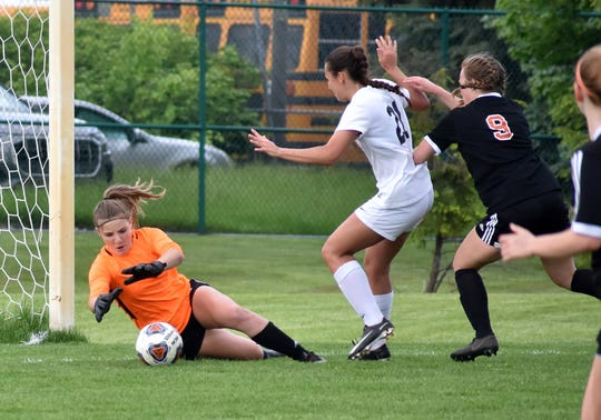 Brighton goalie Sydney Schnurstein makes a save while teammate Kyla Vida (21) shields Northville's Erica Toupin (9) from the ball in a district semifinal at Novi on Wednesday, May 29, 2019.
