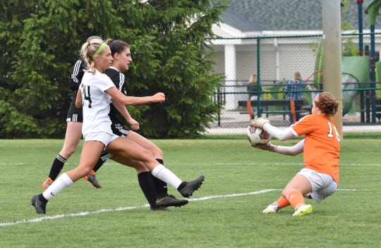 Northville goalie Ellie Thallman makes a save while Brighton's Bryce Calka charges to the net in a district semifinal at Novi on Wednesday, May 29, 2019.