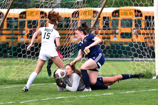 Hartland goalie Cassidy Vaughn makes a save while Novi's Avery Fenchel (15) and Hartland's Lauren Smith (20) converge on the ball in a district soccer semifinal on Wednesday, May 29, 2019.
