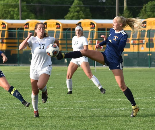Hartland's Justina L'Esperance gets a foot on the soccer ball in front of Novi's Michelle Jecmen (17) in a district semifinal on Wednesday, May 29, 2019.