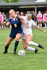 Hartland's Maria Storm (5) and Novi's Jessica Bandyk (16) battle for the soccer ball in a district semifinal on Wednesday, May 29, 2019.