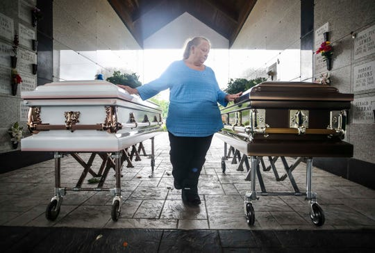 Regina Pughs stands between the caskets of Christina Coy and Douglas Borders Thursday afternoon at the Walnut Ridge Cemetery. Christina Coy was the mother of her grandsons. Pughs praised them both, including Douglas, who helped raise the couple's four boys.