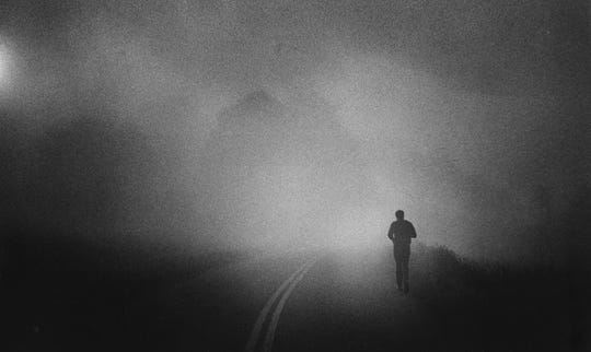 Shrouded in early morning fog, Muhammad Ali takes his daily three-mile run along a Pennsylvania country road. Aug. 24, 1978