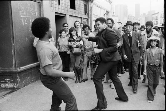 Muhammad Ali engages a young man in a playful sparring match while stopping in San Pedro, California. Ali spotted the people on the street while driving through the community and a stopped to meet them.  Dec. 29, 1979