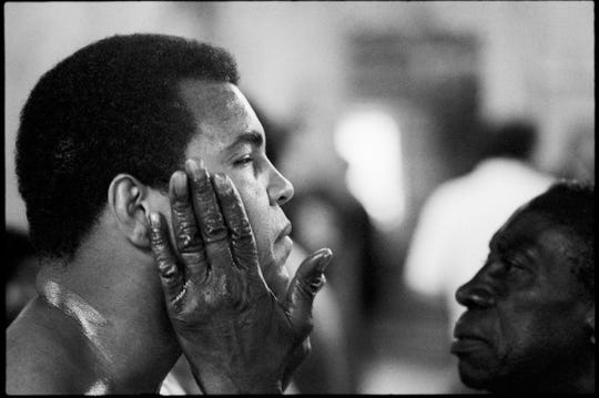 "Louis Sharria works on Muhammad Ali's face while in training at his Deer Lake Pa camp. Sharria served as  Ali's ""cut man"" for many years. 1978"