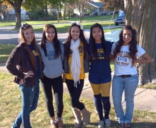 Zoe Halbeisen (pictured in high school second from the right with friends) went to Grand Ledge High School. She was born in China, and connected with her birth parents earlier this year.