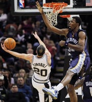 San Antonio Spurs' Manu Ginobili, left, falls as he tries to shoot over Memphis Grizzlies' Hasheem Thabeet during the second half Jan. 29, 2010.