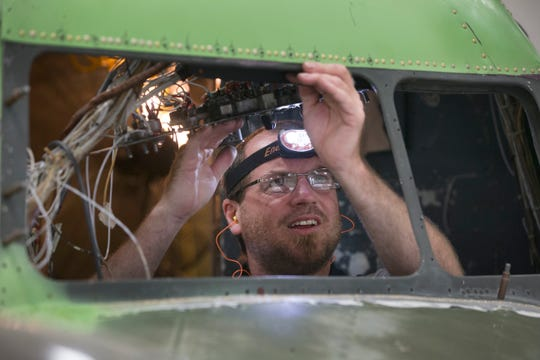 "Jeremy Hoffman works in the cockpit of ""That's All, Brother"" at Basler Turbo Conversions in Oshkosh, Wis. in 2015 to replacement windows could be installed. Five hours before the D-Day beach landings, ""That's All, Brother"" led a formation of more than 800 aircraft dropping 13,000 paratroopers behind enemy lines."