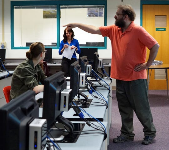 Scott Brielmaier (right) teaches computer science at Hortonville High School, assisted by Erin Draheim (in back), a software engineer who lives in the community. The class is part of an effort sponsored by Microsoft called TEALS that aims to get more students taking computer science and more teachers up to speed to teach it.